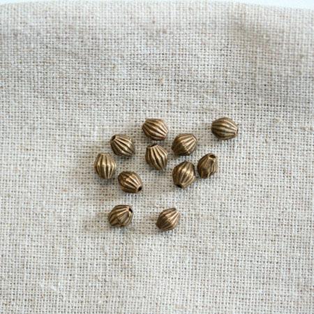 Perle métal 5x6mm Bronze vieilli Bicône à rayures x 180